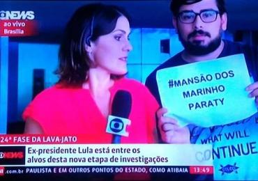 Homem interrompe repórter com cartaz Mansão dos Marinho em transmissão ao vivo na Globo News