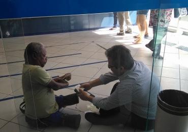 Gerente de banco senta no chão para atender a homem com deficiência e comove internautas