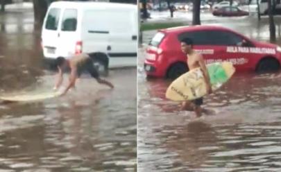 Homem é flagrado 'surfando' na rua durante chuva em Goiânia